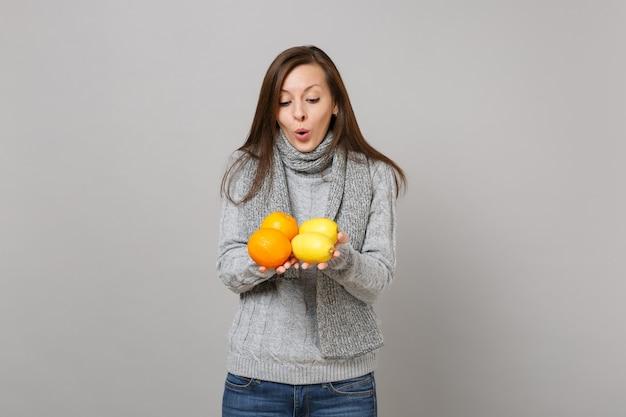 Пораженная молодая женщина в сером свитере, удерживании шарфа, глядя на лимоны и апельсины, изолированные на сером фоне. концепция холодного сезона людей здорового образа жизни моды искренние эмоции. копируйте пространство для копирования.