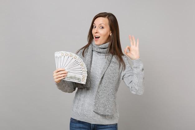 Изумленная молодая женщина в сером шарфе свитера, показывающая жест ок, держит много кучу долларов наличных денег, изолированных на сером фоне. эмоции людей здорового образа жизни моды, концепция холодного сезона.