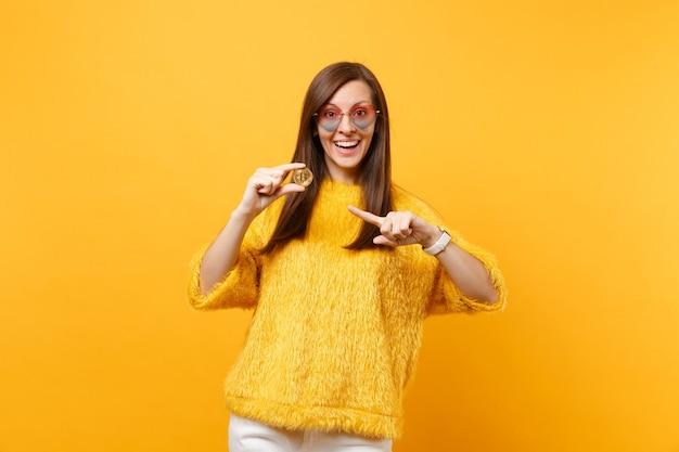 비트코인에 검지 손가락을 가리키는 하트 안경을 쓴 젊은 여성, 황금색 금속 동전, 노란색 배경에 격리된 미래 통화. 사람들은 진실한 감정, 라이프 스타일. 광고 영역입니다.