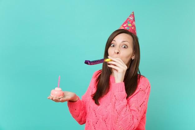 파란색 청록색 벽 배경에 격리된 촛불과 함께 손 케이크를 들고 파이프를 들고 있는 분홍색 스웨터와 생일 모자를 쓴 젊은 여성을 놀라게 했습니다. 사람들이 라이프 스타일 개념입니다. 복사 공간을 비웃습니다.