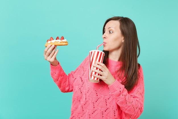 Amazed young woman in knitted pink sweater looking on eclair cake and drinking cola or soda from plastic cup isolated on blue background, studio portrait. people lifestyle concept. mock up copy space.