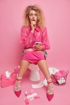 놀란 젊은 여성은 설사 때문에 중요한 회의를 놓치고 충격을 받은 휴대폰을 들고 분홍색 벽에 대고 변기에 우아한 옷을 입고 전화를 기다립니다. 변비