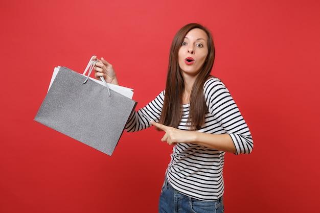 밝은 빨간색 벽 배경에서 격리된 손에 쇼핑을 한 후 구매한 패키지 가방에 검지 손가락을 가리키는 놀란 젊은 여성. 사람들은 진심 어린 감정, 라이프 스타일 개념입니다. 복사 공간을 비웃습니다.