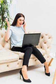Amazed young woman sitting on couch with laptop and talking by phone