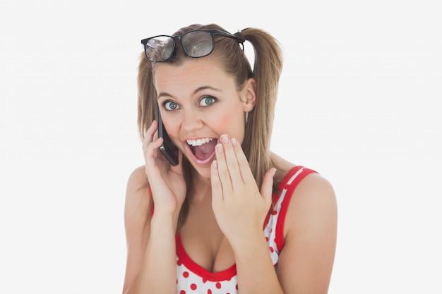 携帯電話を使用して驚いた若い女性