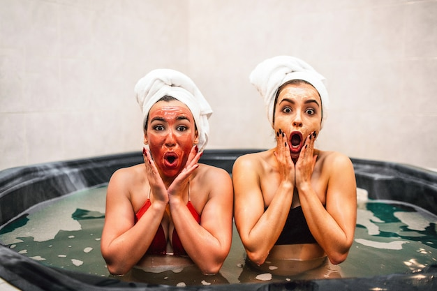 Amazed young women sit in hydromassage bath and do beauty procedures. they have chill and relax. models look wondered. they touch face with hands.