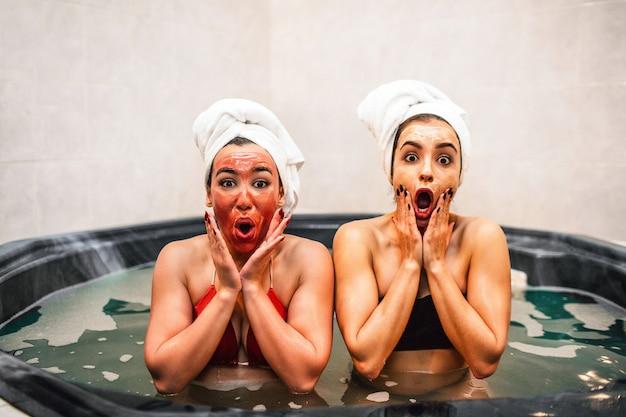 놀란 젊은 여성들은 수압 마사지 욕조에 앉아 미용 절차를 수행합니다. 그들은 차갑고 긴장을 풀고 있습니다. 모델이 궁금해 보입니다. 그들은 손으로 얼굴을 만집니다.