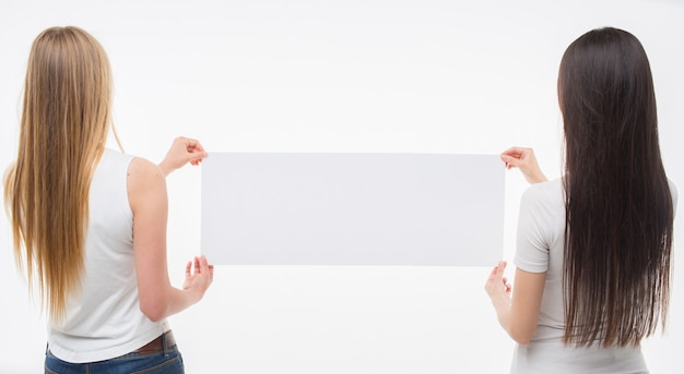 Amazed young women stand and hold piece of white paper