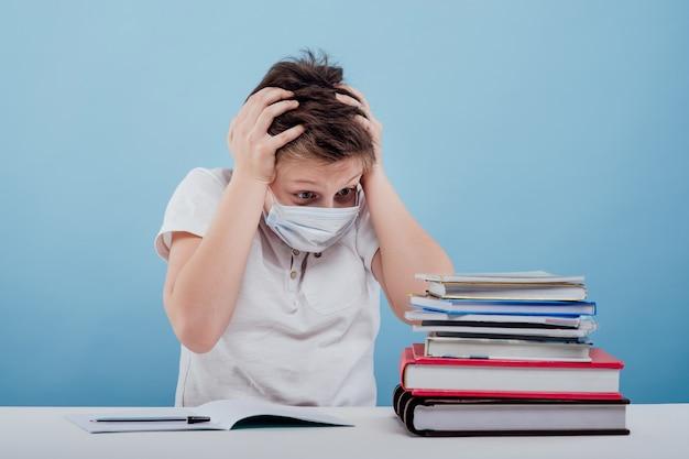 파란색 배경에 격리된 탁자에 앉아 있는 책을 보고 있는 의료용 마스크를 쓴 놀라운 소년