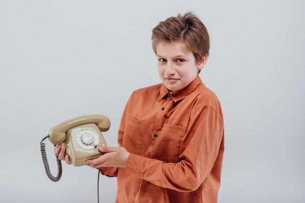 흰색 배경에 격리된 카메라를 쳐다보는 오래된 전화를 가진 놀란 소년
