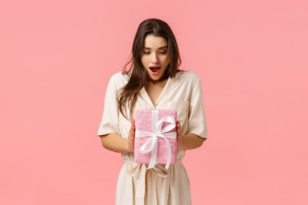 Amazement, celebration and holidays concept. surprised girlfriend holding box of present, didnt expact receive gift, open mouth fascinated look touched wrapped box, pink background