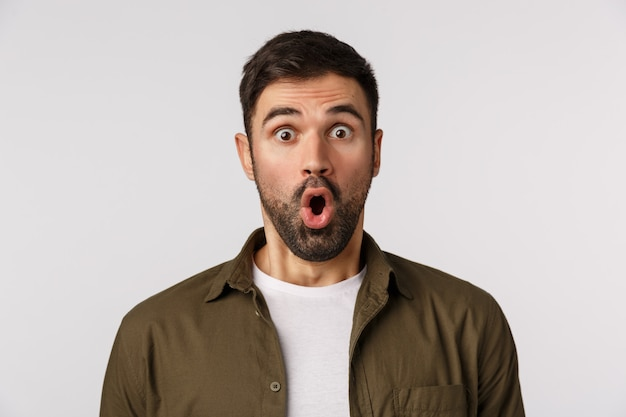 Amazement, emotions and people concept. close-up astonished, fascinated man in awe, with beard, folding lips gasping speechless and amazed, see thing he wanted with large discount