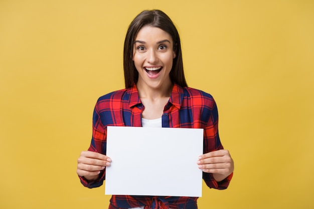 Amazement or surprised female with blank white panel, isolated on yellow background.