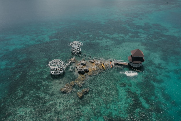 Amazing aerial shot of a luxurious cottage in the middle of the blue ocean water