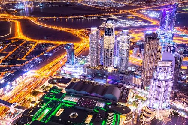 조명된 고층 빌딩이 있는 놀라운 공중 스카이라인 도시 풍경. 밤에 두바이 시내, 아랍 에미리트.