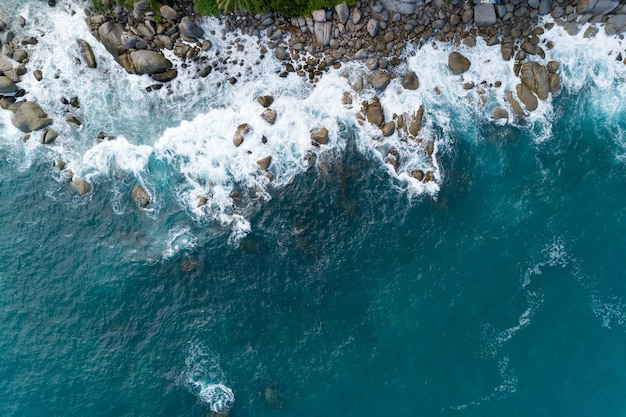 Amazing aerial view of crashing waves on rocks seascape nature view and beautiful tropical sea with sea coast view in summer season image by drone high angle view