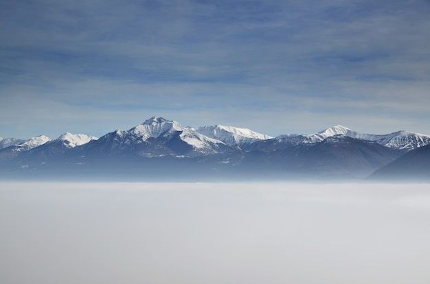 Amazing aerial view of mountains partially covered with snow and positioned higher than clouds