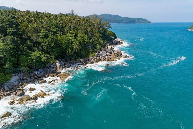 岩に打ち寄せる波の素晴らしい空中写真海の景色自然の景色と夏の海岸の景色を望む美しい熱帯の海ドローンによる画像ハイアングルビュー旅行とウェブサイトの背景のコンセプト