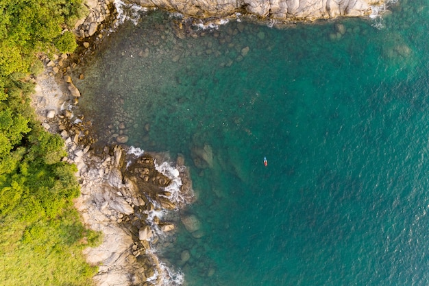 プーケット島に沈む海岸の崖の素晴らしい空撮。澄んだターコイズブルーの海でカヤックボートと空中海景、夏の波。透明な海。トップビューボートは海岸の自然を通過