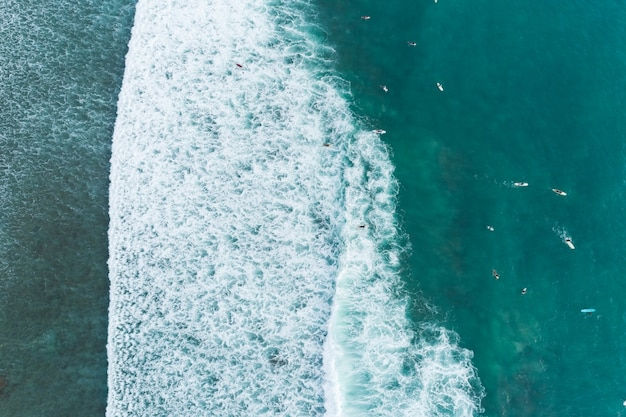 Amazing aerial view top down of waves break on tropical sea surfers with surfing boards aerial drone view of sea waves on the beautiful ocean at phuket thailand.
