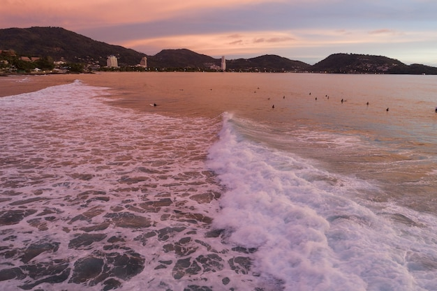 Amazing aerial view waves break on tropical sea surfers with surfing boards aerial drone view of sea waves with beautiful sunset or sunrise sky at phuket thailand.