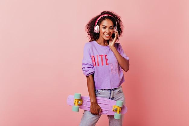 스케이트 보드와 함께 포즈 보라색 스웨터에 놀라운 아프리카 여자. 헤드폰에 분홍색에 debonair 흑인 여성 모델 서.