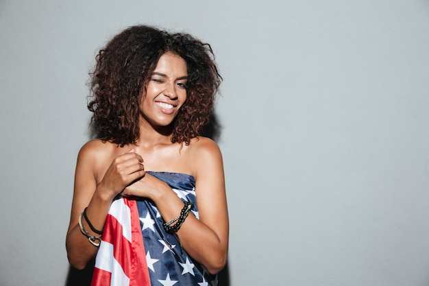 Amazing african young lady standing dressed in usa flag