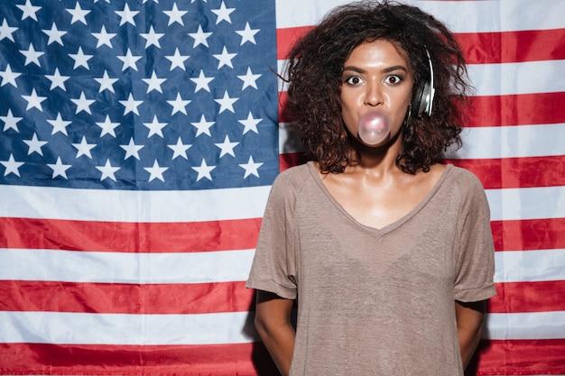 Изумительная африканская молодая женщина с жевательной резинкой