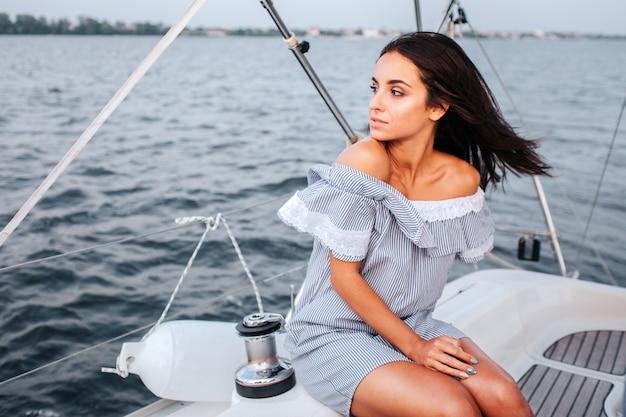 Удивительная и красивая молодая женщина сидит на борту яхты и смотрит налево.