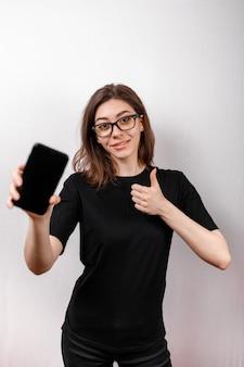 Изумительная и милая европейская женщина держа смартфон в правой руке пока усмехающся, делающ рекламу