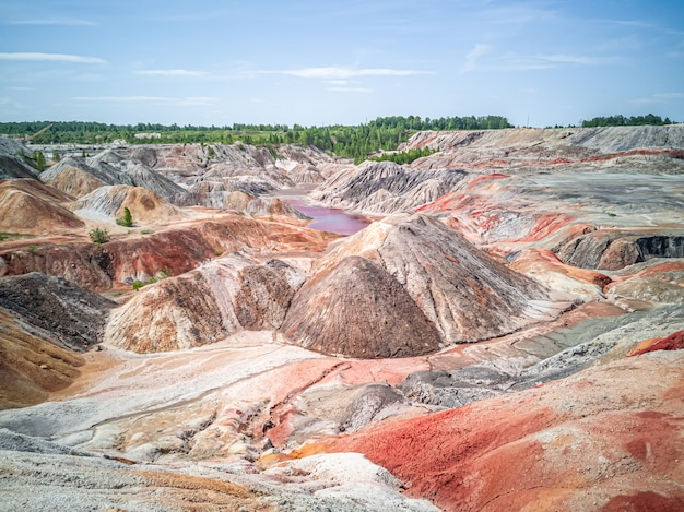 Amazing  apocalyptic landscape like a planet mars surface. solidified red-brown black earth surface. barren, cracked and scorched land. global warming concept. refractory clay quarries.