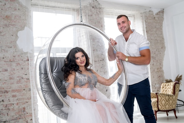 Amazing attractive and pregnant pair posing near window