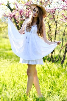 Amazing attractive young woman with long hair, in hat, white light dress enjoying spring sunny day in garden on blooming sakura background.