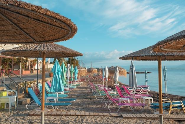 Удивительная бухта с чистой водой на острове корфу, греция. красивый пейзаж пляжа ионического моря с красочными шезлонгами и зонтиками.