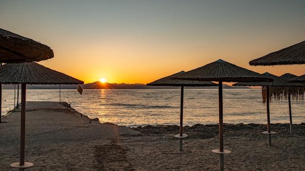 코르푸 섬, 그리스의 paleokastritsa에서 맑은 물과 함께 놀라운 베이. 짚 우산, 일몰 이오니아 바다 해변의 아름 다운 풍경.