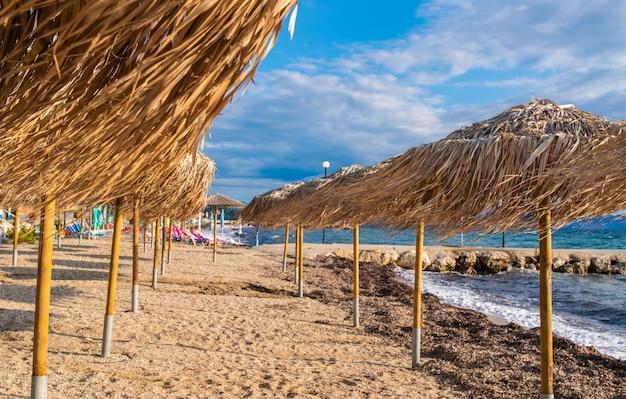 코르푸 섬, 그리스에 맑은 물과 함께 놀라운 베이. 짚 우산, 화창한 날 이오니아 바다 해변의 아름 다운 풍경.