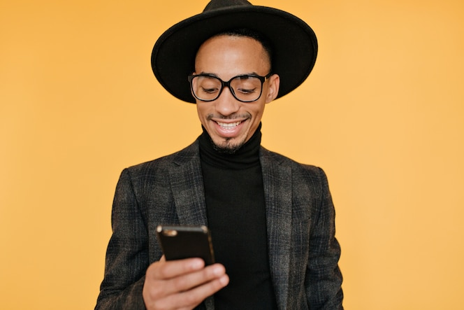 Amazing bearded african guy texting message.glad mulatto male model looking at his phone with smile.