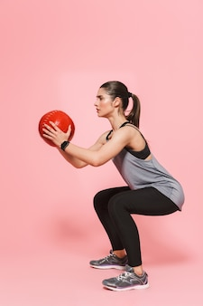 驚くべき美しい若いかなりフィットネスの女性は、ピンクの壁に分離されたボールでスポーツエクササイズを行います Premium写真