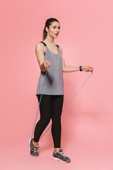 놀랍고 아름다운 젊고 예쁜 피트니스 여성은 분홍색 벽에 격리된 줄넘기를 건너뛰며 스포츠 운동을 합니다