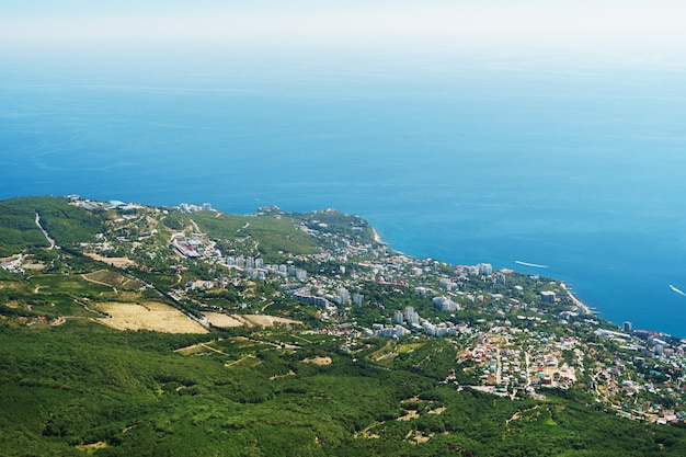Удивительный вид с высоты птичьего полета на город ялту, с черным морем, простирающимся до самого горизонта.