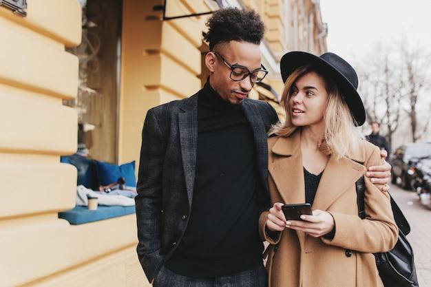 彼女のアフリカの友人に興味を持って見ている素晴らしいブロンドの女の子。一緒に時間を過ごすトレンディな衣装の若者の屋外の肖像画。