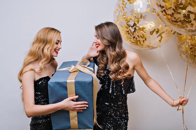 素晴らしいブロンドの女の子は、薄茶色の髪の女友達から大きなプレゼントを受け取りました。パーティーの風船を保持しているブルネットの妹への贈り物を保持している魅力的な若い女性の屋内ポートレート。