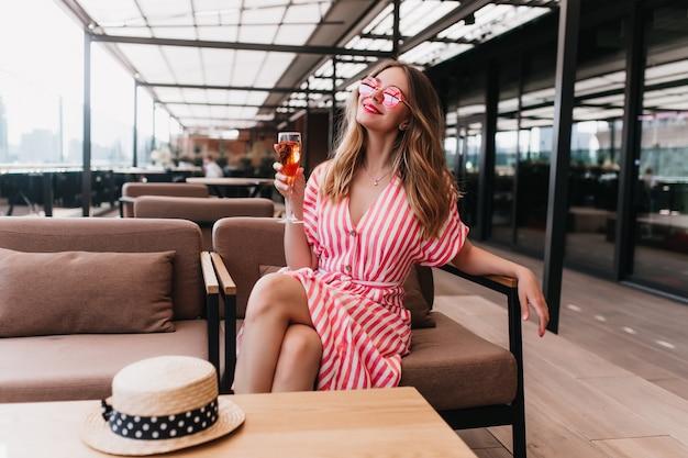 Incredibile signora bionda in occhiali da sole che riposa nella caffetteria. foto interna di bella giovane donna in abito estivo in posa con un bicchiere di champagne nel fine settimana.