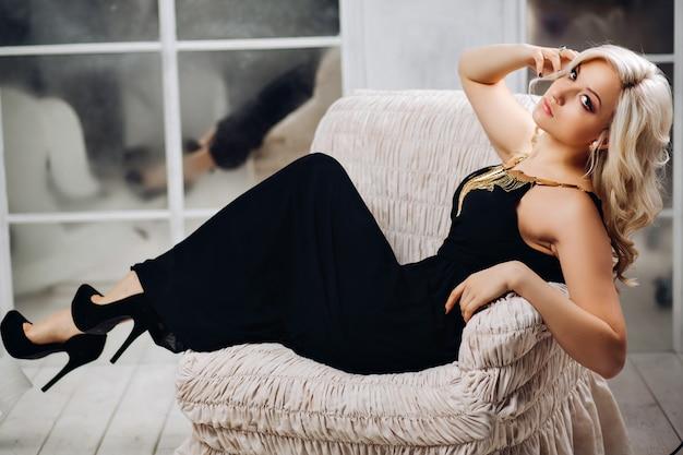 素晴らしいブロンドの女性の爪にゴールドメッキのジュエリースタイリッシュなマニキュアとトレンディな化粧品で豪華な白い椅子に座っているエレガントな黒のドレスでシックな長いブロンドの巻き毛の美しいセクシーな女性