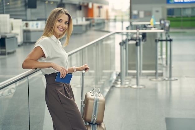 Удивительная блондинка демонстрирует свою улыбку, опираясь на опору, стоит аккуратный чемодан