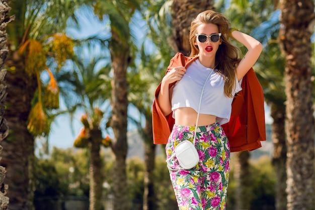 屋外でポーズトレンディな夏の服装で素晴らしいブロンドの女性