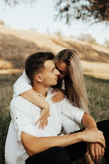Amazing blonde woman is leaning her head on her boyfriend outside while dating. she hugs him