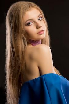 スタジオでポーズをとっている裸の肩を持つ長い青々とした髪と青いドレスの素晴らしいブロンドの女性
