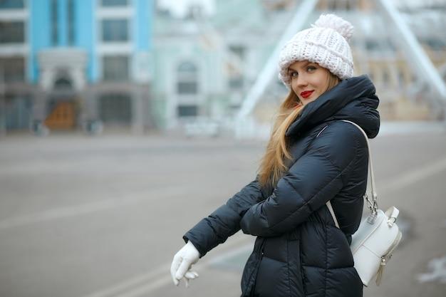 街歩きを楽しんで、ニット帽をかぶった赤い口紅を持つ素晴らしいブロンドの女性。テキスト用のスペース