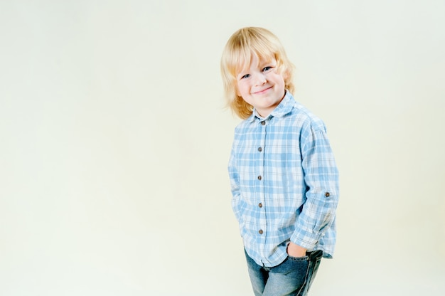 Amazing blue eyes and innocence of cute blond hair of a 5 year old boy. simple portrait, who is wearing a blue shirt